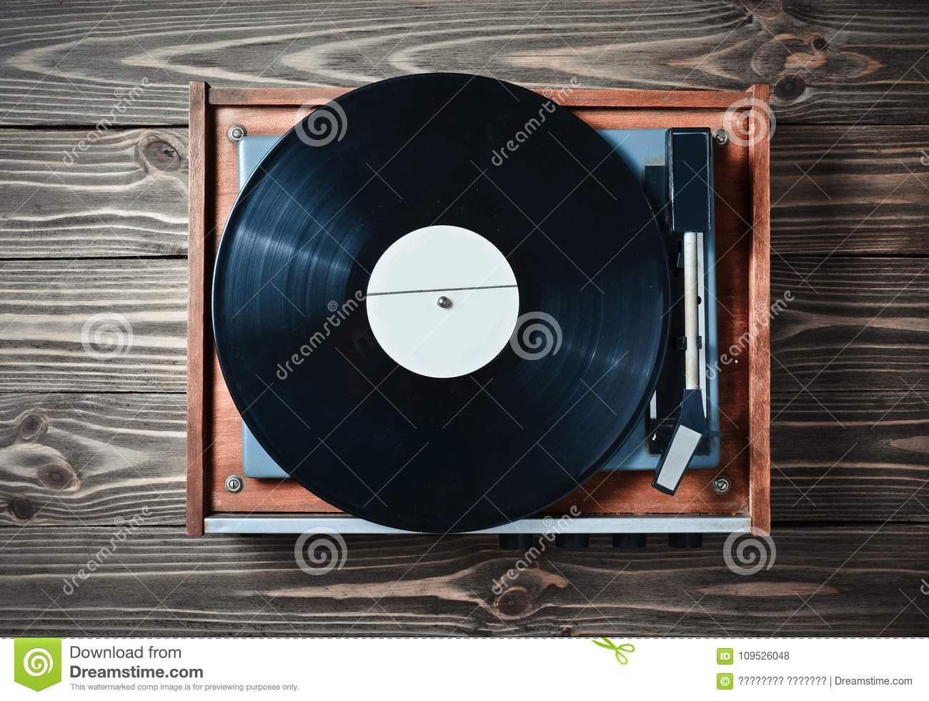Vinyl player with plates on a wooden table. Entertainment 70s. Listen to music.