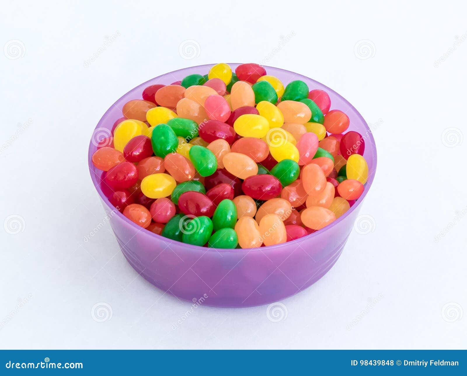 Violette plastic ronde middelgrote groottekom voor losse die producten met gekleurde kleine die snoepjes worden gevuld op een wit