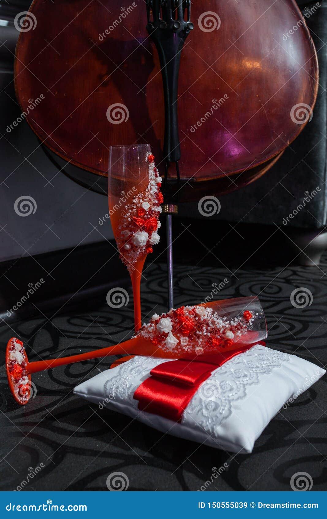 Violoncelo e dois copos de vinho vermelhos no descanso