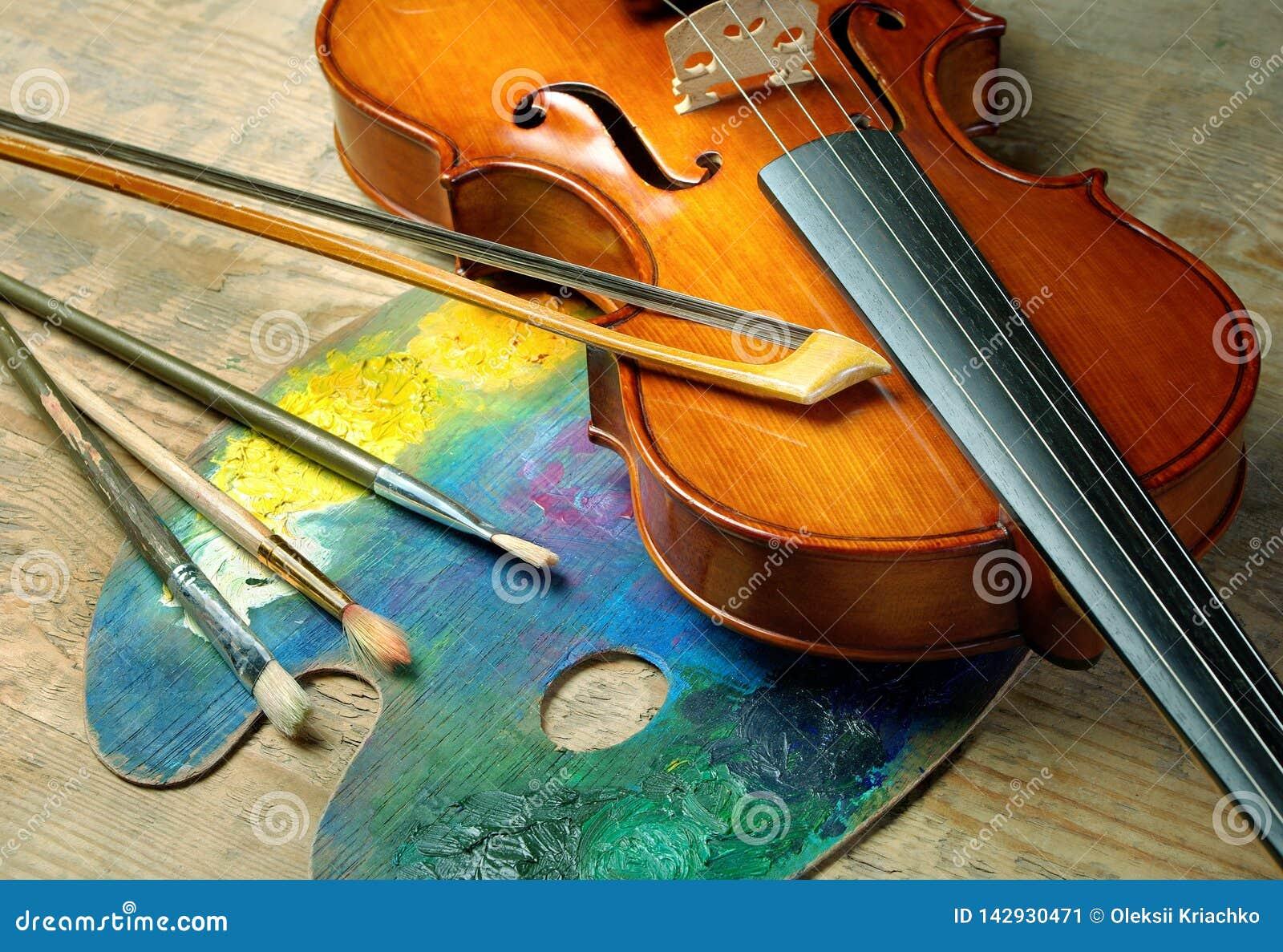 Viool, borstels en palet op een houten achtergrond