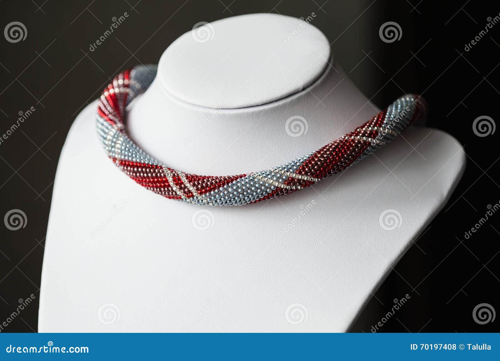 Virkning prydd med pärlor halsband med en modell
