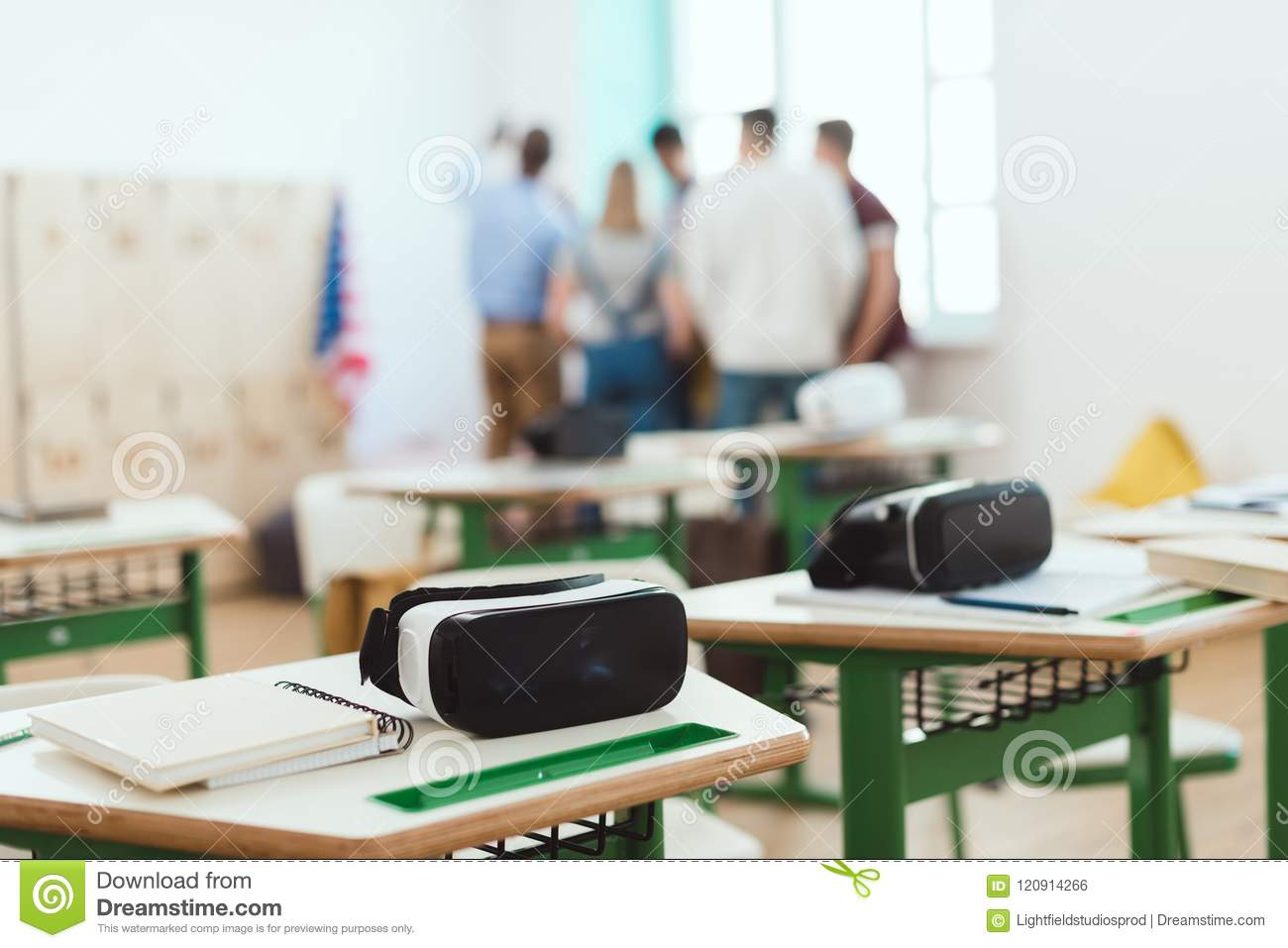 Virtual reality headsets on tables with teacher and high school students standing behind