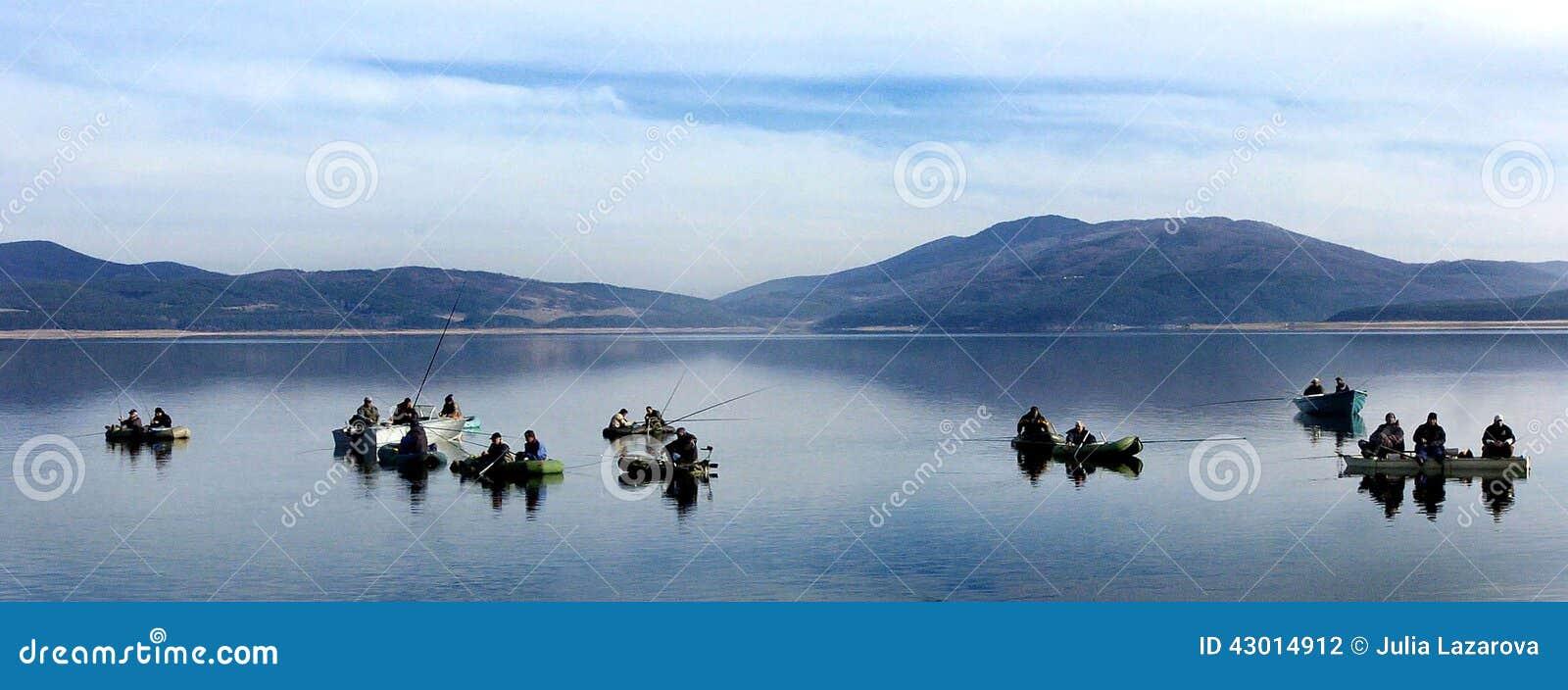 Vis-mens die op het meer vissen