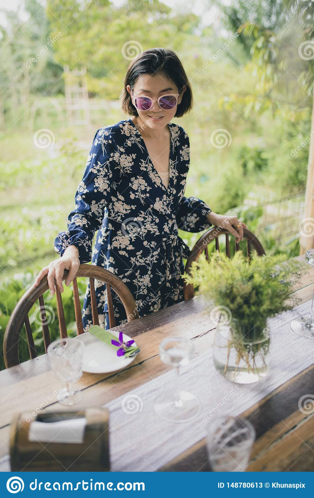 Visage de sourire toothy de belle femme asiatique avec émotion de détente près de table de nourriture