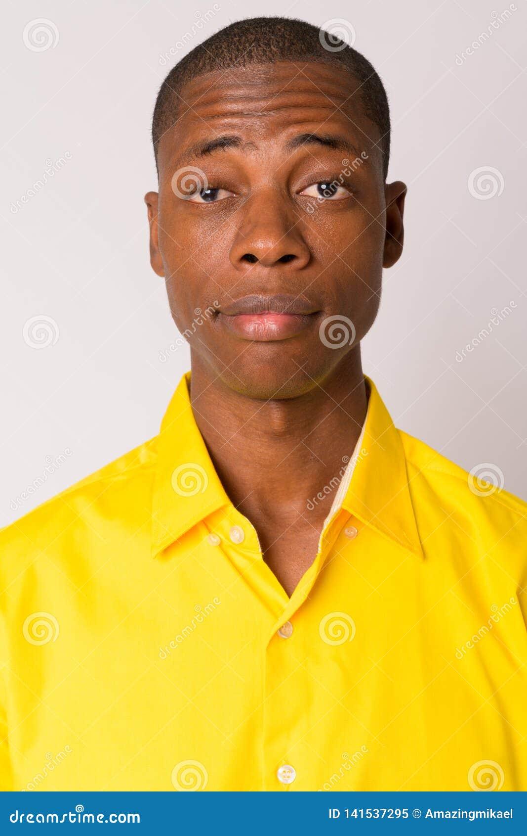 Visage du jeune homme d affaires africain chauve bel utilisant la chemise jaune