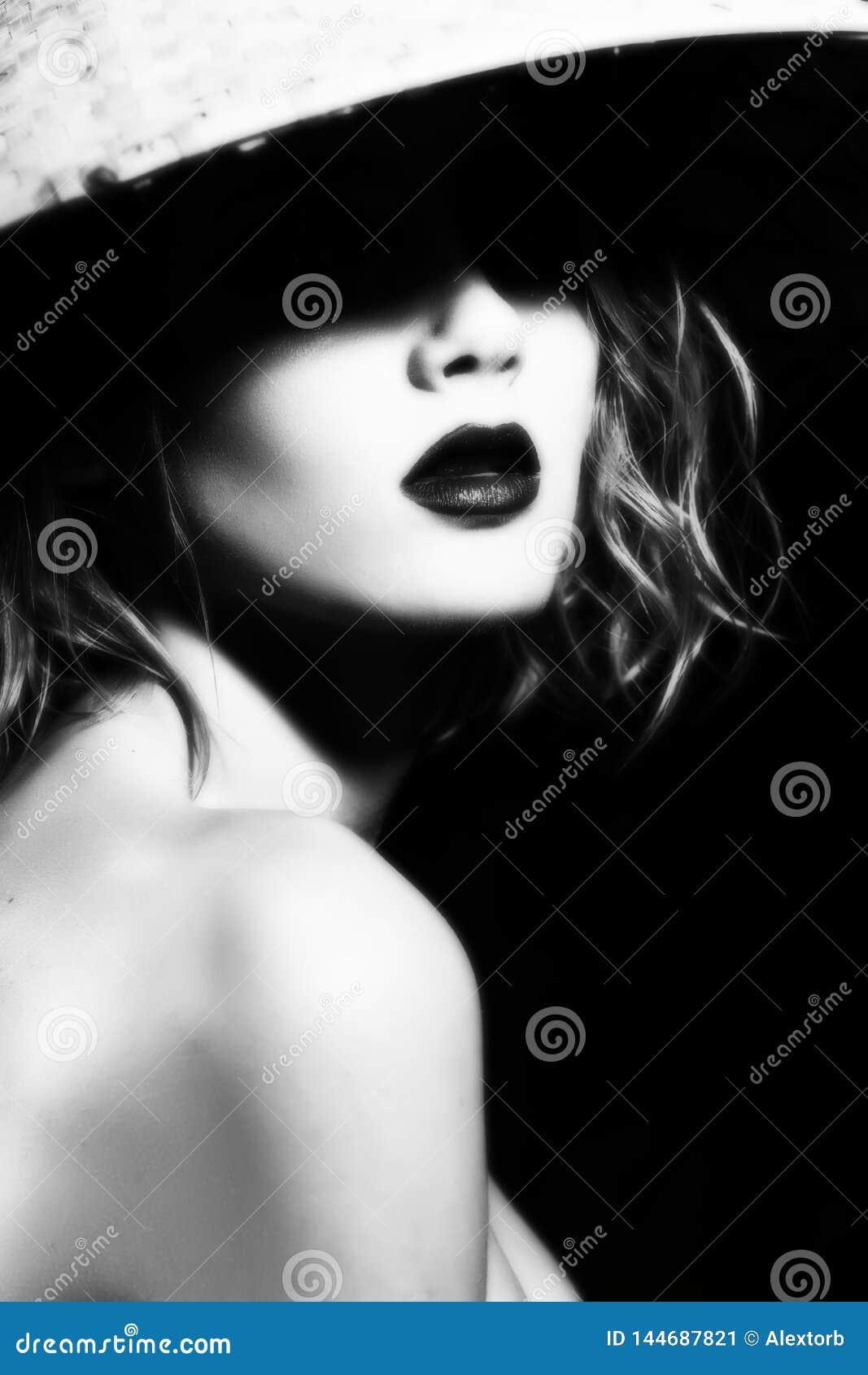 Visage en gros plan d une belle jeune fille blonde avec les l?vres rouges et les yeux cach?s dans l ombre d un chapeau asiatique