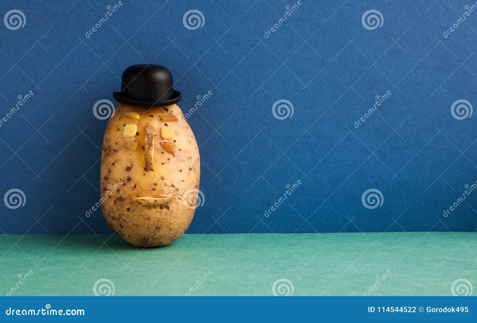 Visage sérieux de chapeau de lanceur de Senor Potato Légume démodé de style sur le fond bleu de plancher de vert de mur Copiez l