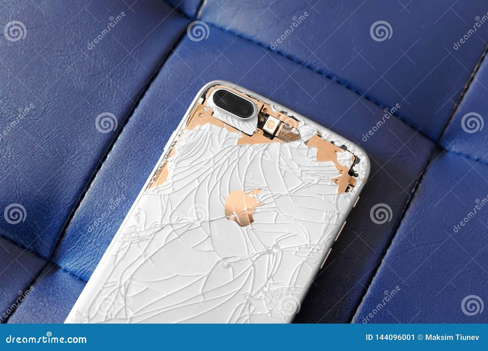 VISAGINAS LITAUEN - MARS 30, 2019: Den tillbaka sidan av en bruten iPhone 8 plus är vit, och guld- på en blått piska bakgrund