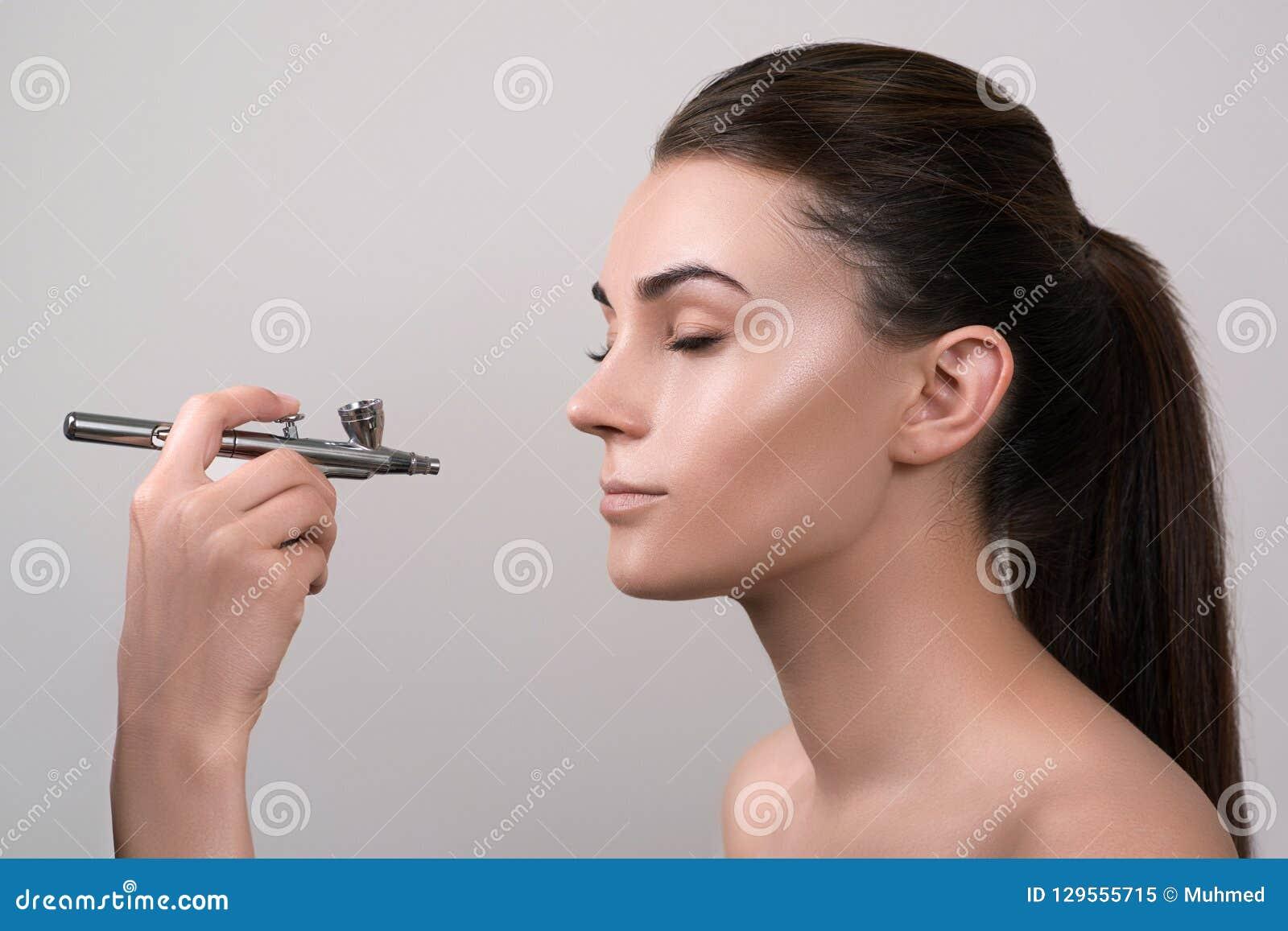 Visagist che fa trucco per il modello con l aerografo, isolato su grigio Fondo con l aerografo della tenuta della mano Visagist f