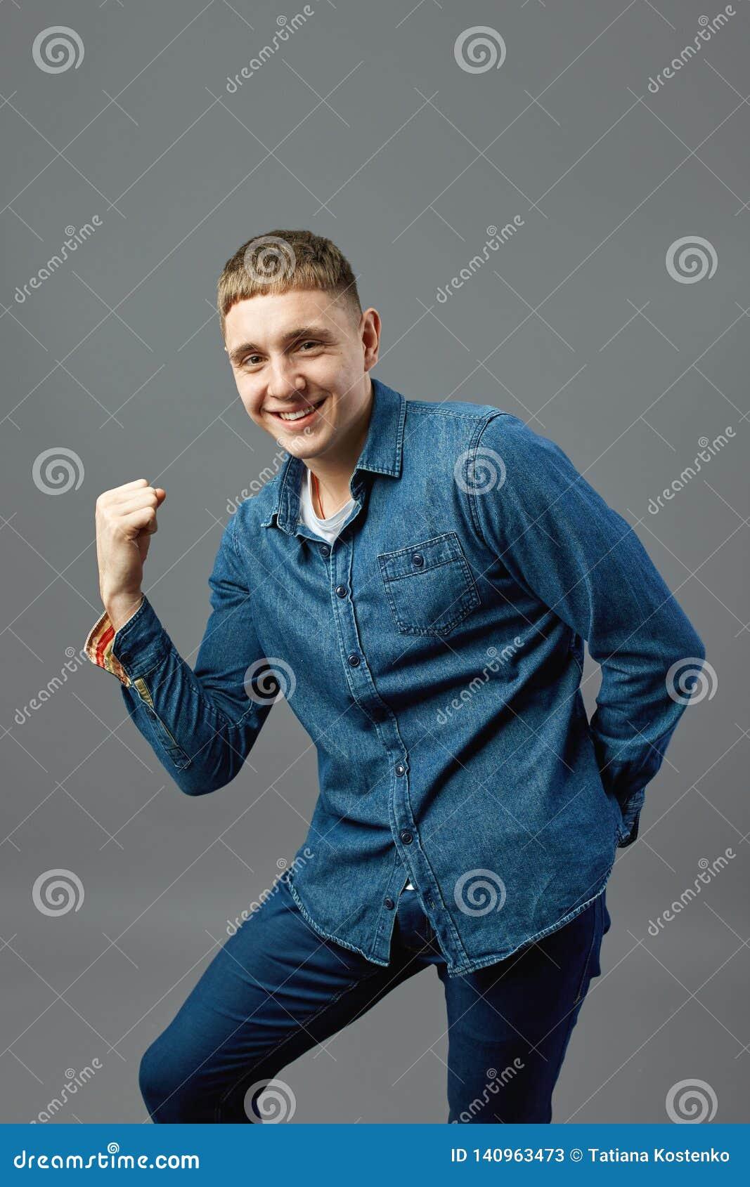Visar den iklädda a jeansskjortan för rolig grabb hans makt med hans hand i studion på den gråa bakgrunden