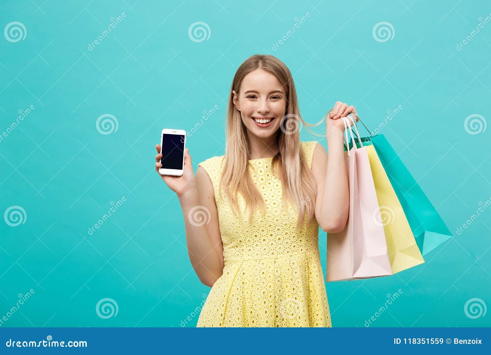 Visar den unga attraktiva kvinnan för ståenden med shoppingpåsar skärmen för telefon` s direkt till kameran Isolerat på blått