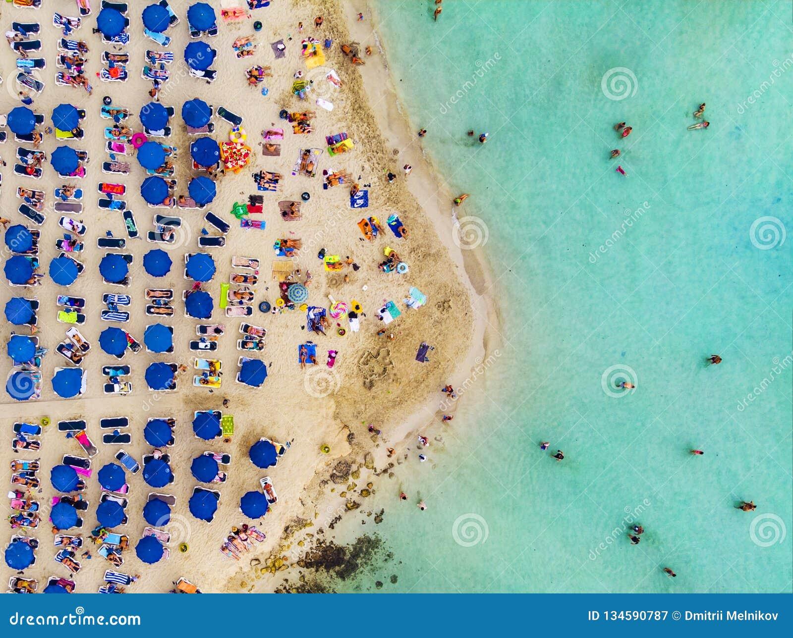 Visión aérea que sorprende desde arriba sobre la playa de Nissi en Chipre Playa de Nissi en la alta marea Los turistas se relajan