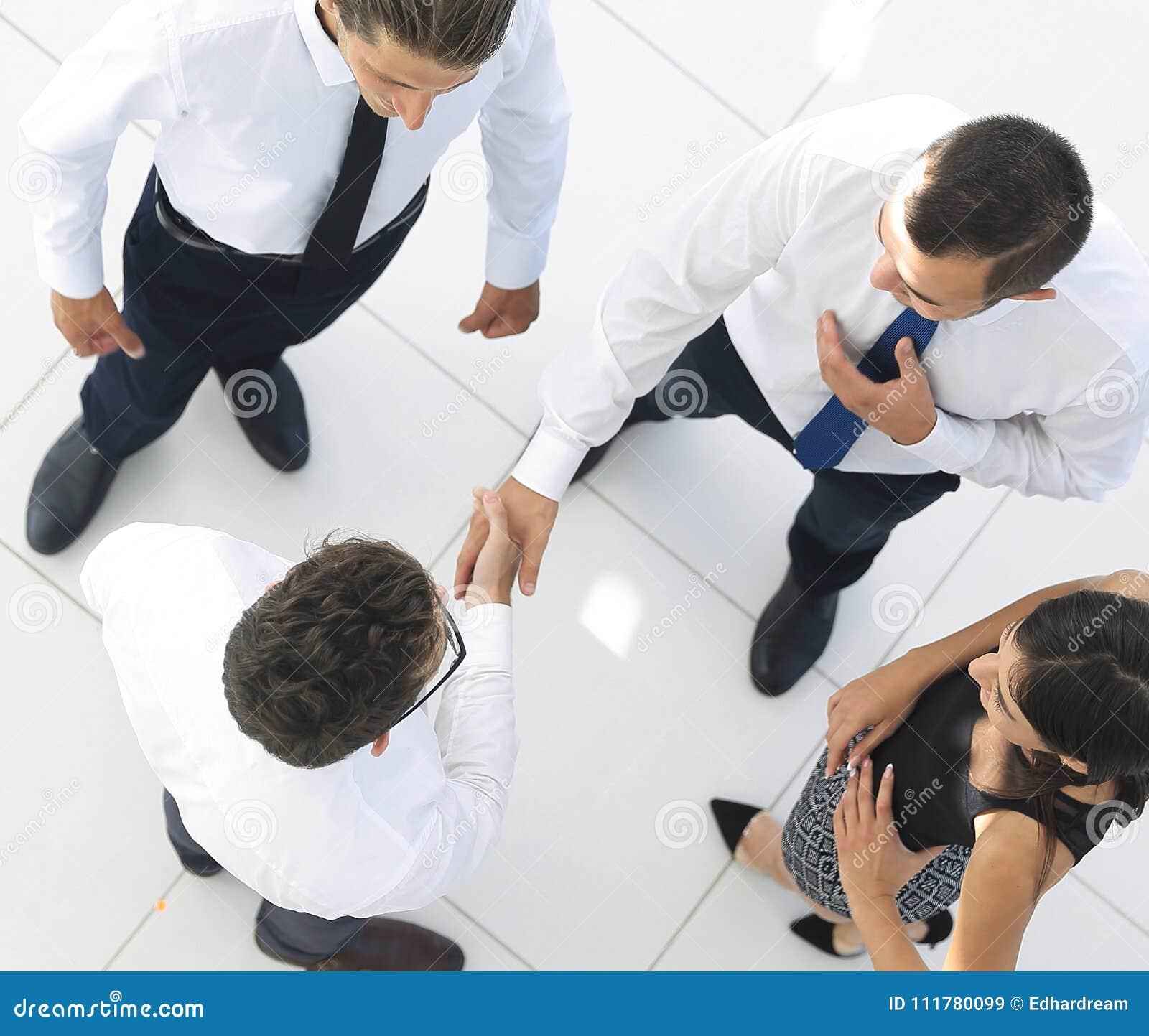 Visión desde la tapa colegas que sacuden las manos en pasillo de la oficina