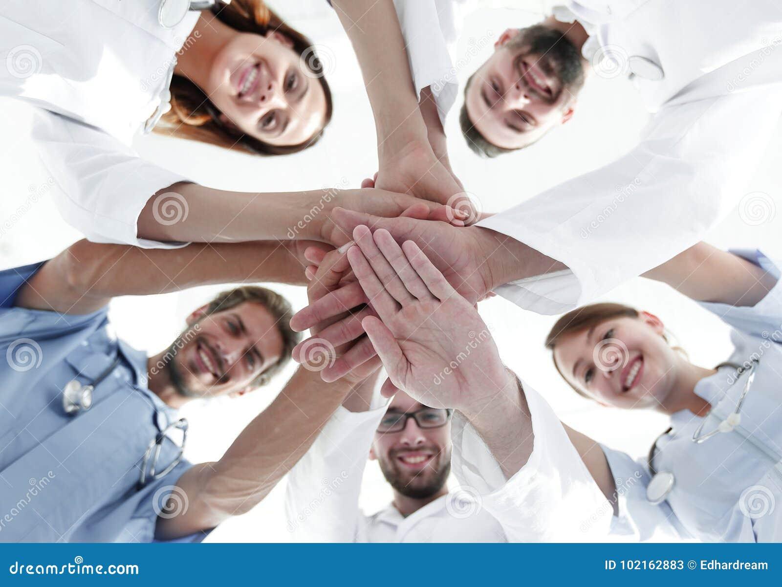 Visión inferior un equipo de doctores en el centro médico abrochó sus manos juntas