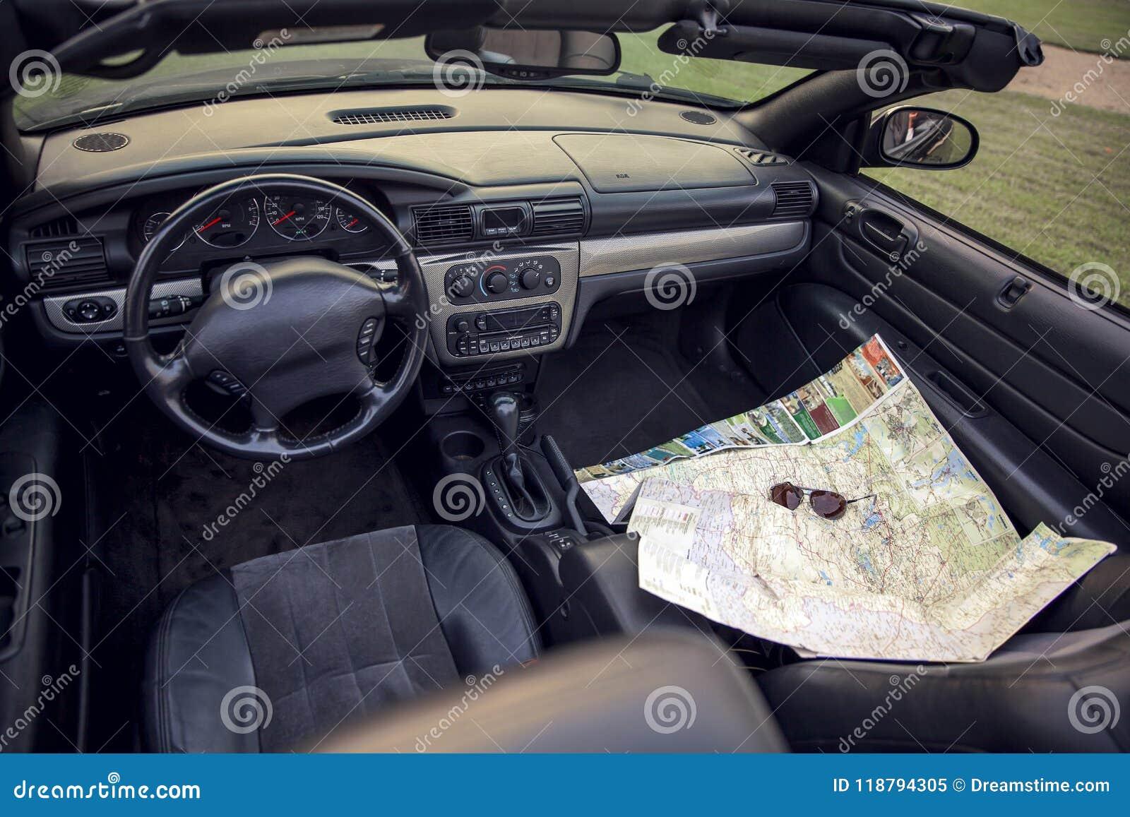 Visión por dentro de un coche en un tablero de instrumentos con un mapa y los vidrios de camino Tema del recorrido