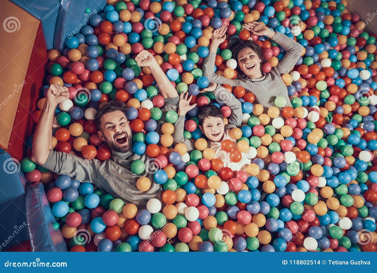 Visión superior Familia feliz que miente en piscina con las bolas