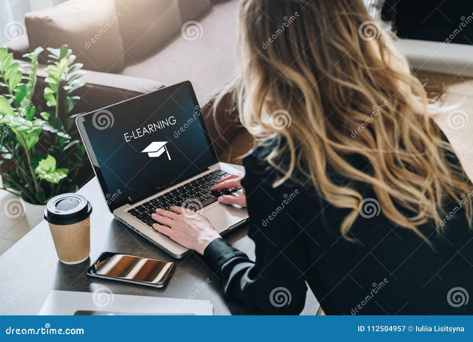 Visión trasera La mujer joven está trabajando en el ordenador portátil con la inscripción en aprendizaje electrónico de la pantal