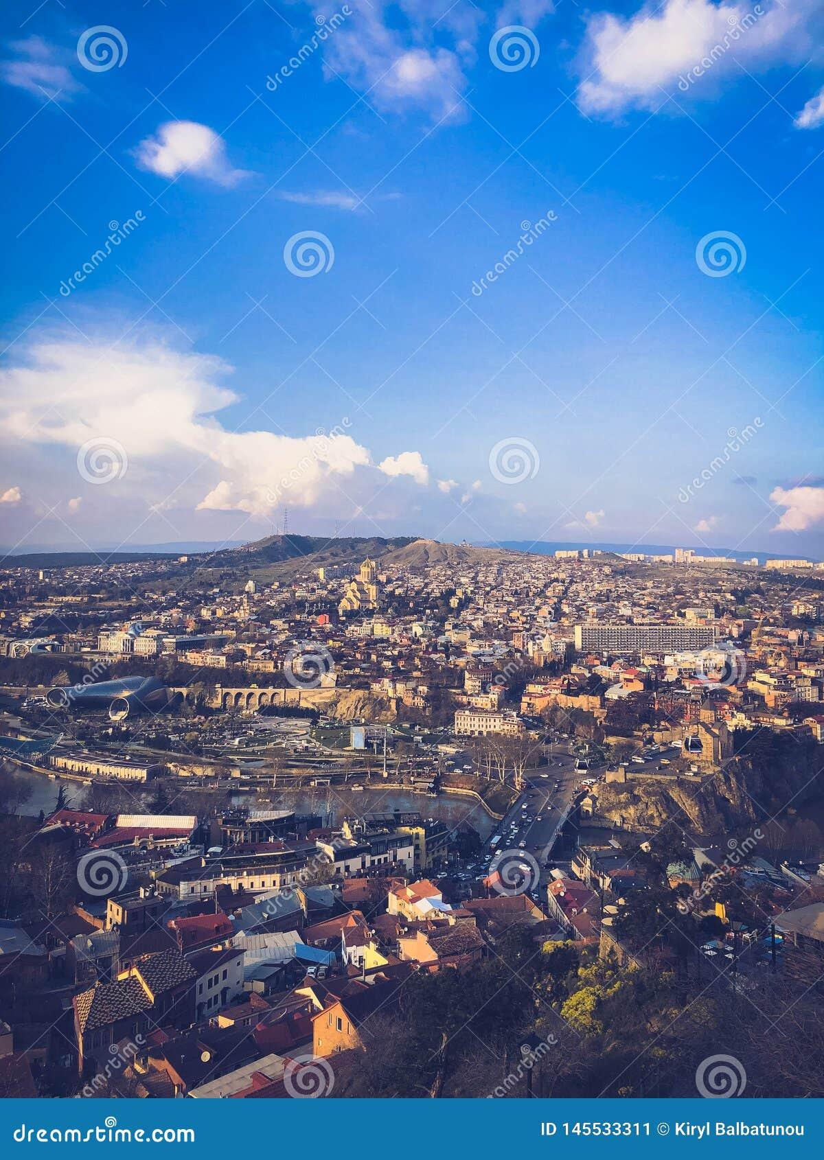 Visi?n vertical desde el top de una altura de una ciudad tur?stica hermosa con los edificios y las casas, de tejados de ?rboles y