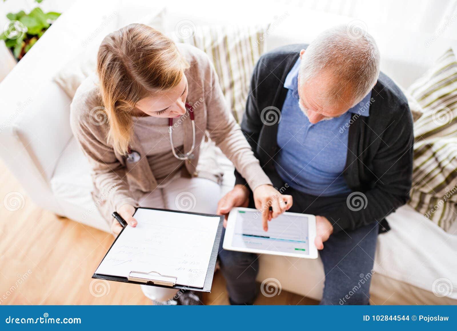 Visitante da saúde e um homem superior com a tabuleta durante a visita home