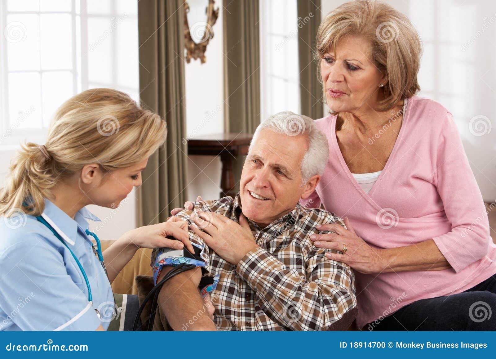 Visitante da saúde que toma a pressão sanguínea de homem sênior