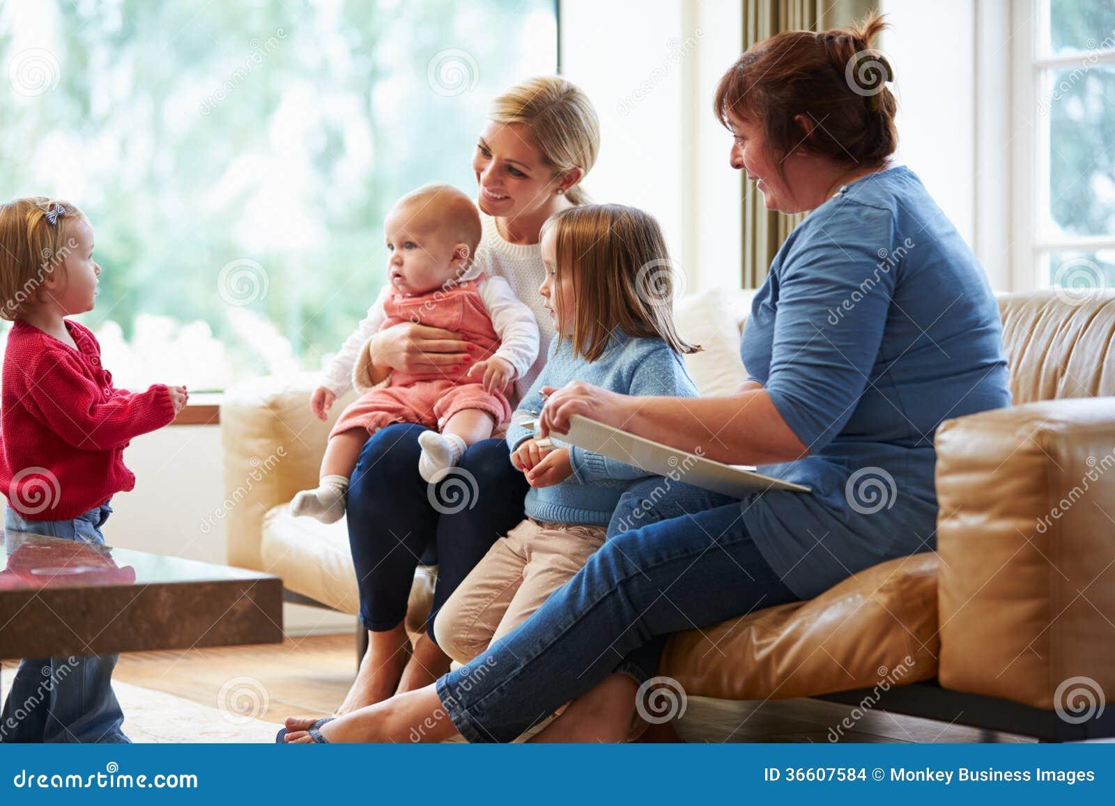 Visitante de la salud que habla con la madre con los niños jovenes