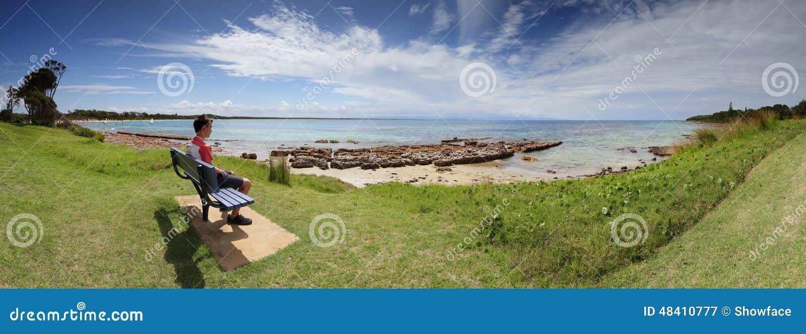 Visitante turístico que admira la playa Australia de Currarong de las opiniones