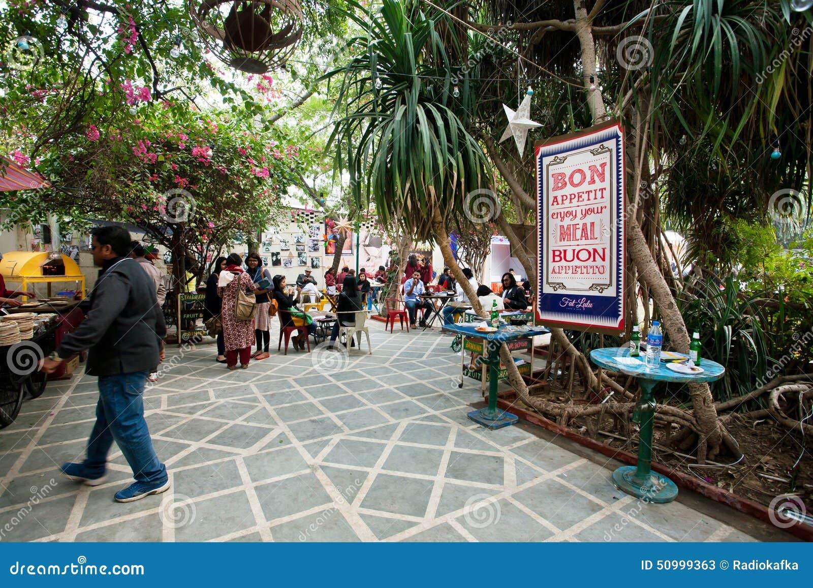 Visitantes del café al aire libre que se sientan debajo de los árboles tropicales