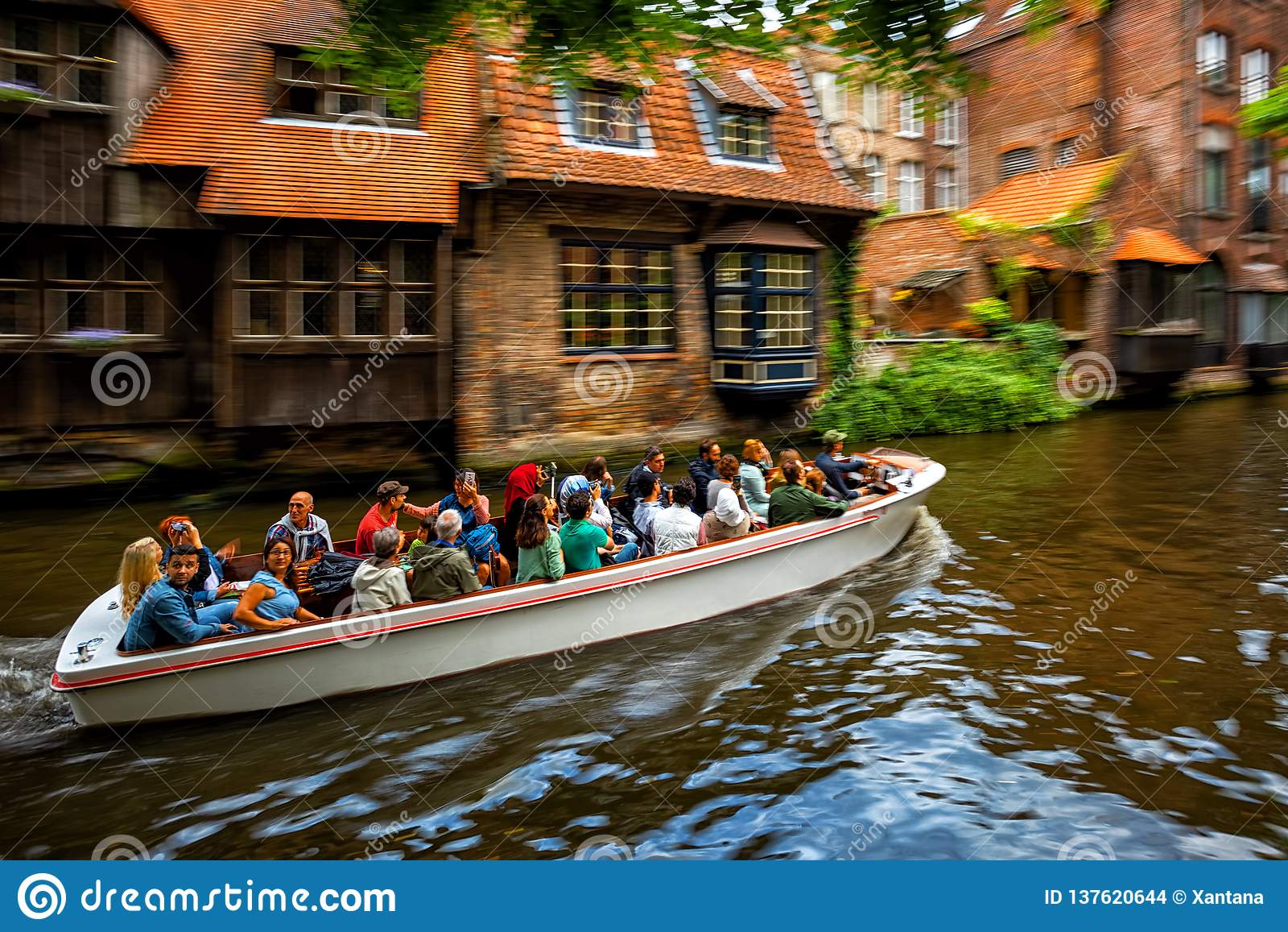 Visite de touristes de bateau de canal dans la vieille ville de Bruges, Belgique