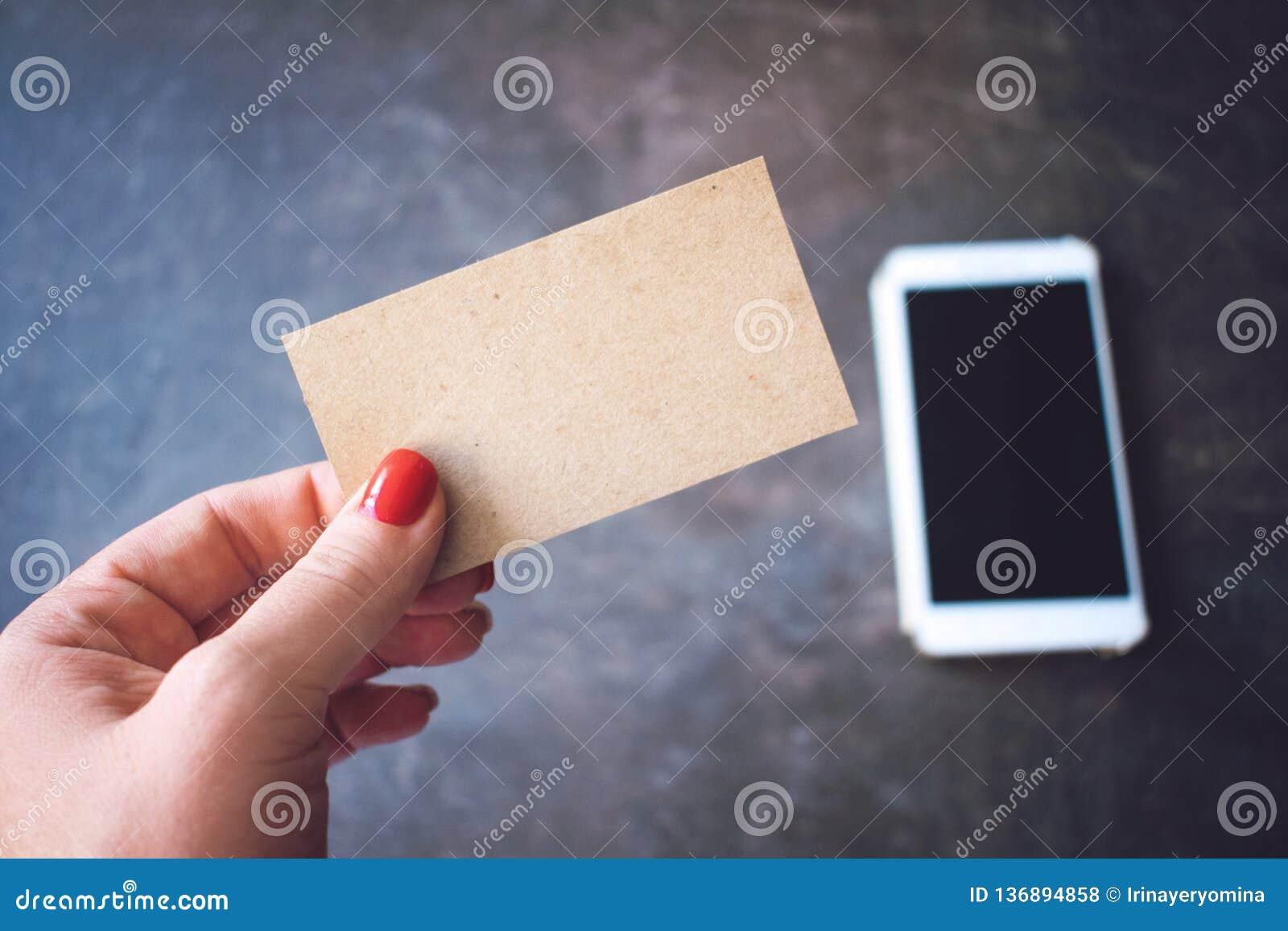 Visitenkartemodell Frauen übergeben das Halten der leeren PapierVisitenkarte auf defocused Smartphone- und Notizbuchhintergrund