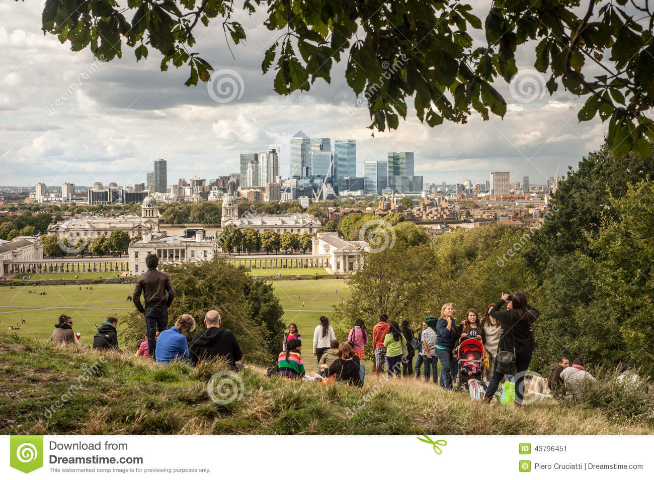 Visitors enjoy the view of the Canary Wharf skyscrapers from Greenwich park in London