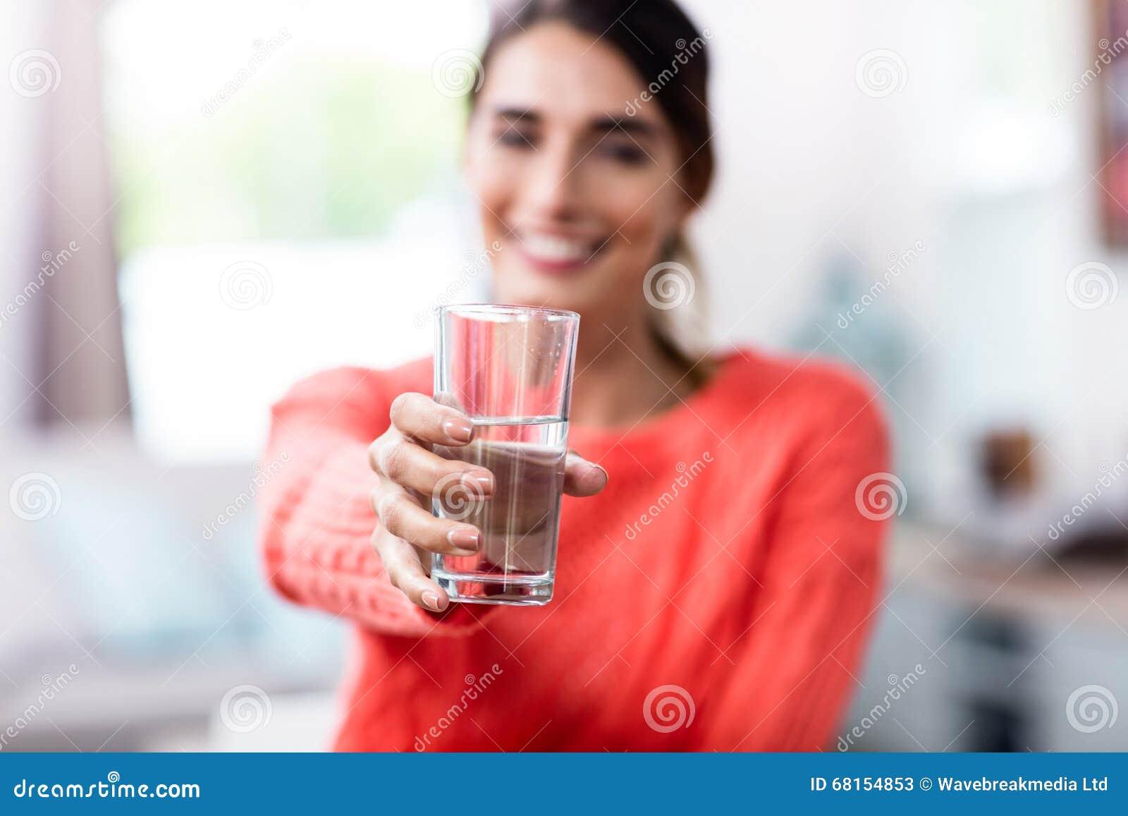 Visning för ung kvinna som dricker exponeringsglas med vatten