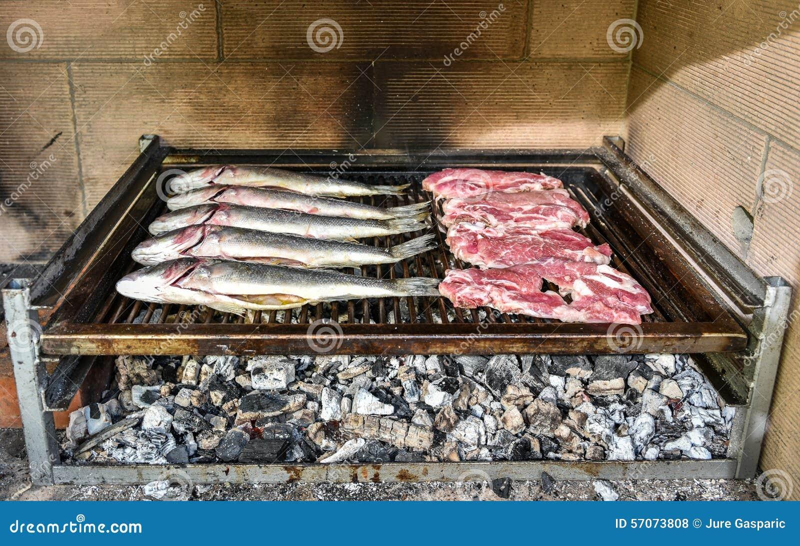 Vissen en lapje vlees op de houtskoolgrill