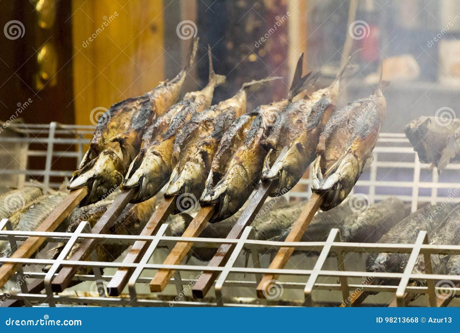 Vissen van de barbecue de stokvis geroosterde forel op voorraden met brandrook