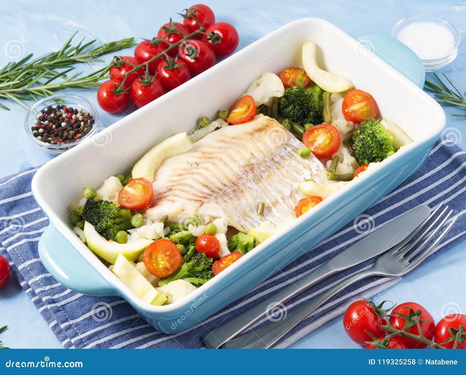 Vissenkabeljauw in blauwe oven met groenten wordt gebakken - broccoli, tomaten die Gezond dieetvoedsel Arduinsteenachtergrond, zi