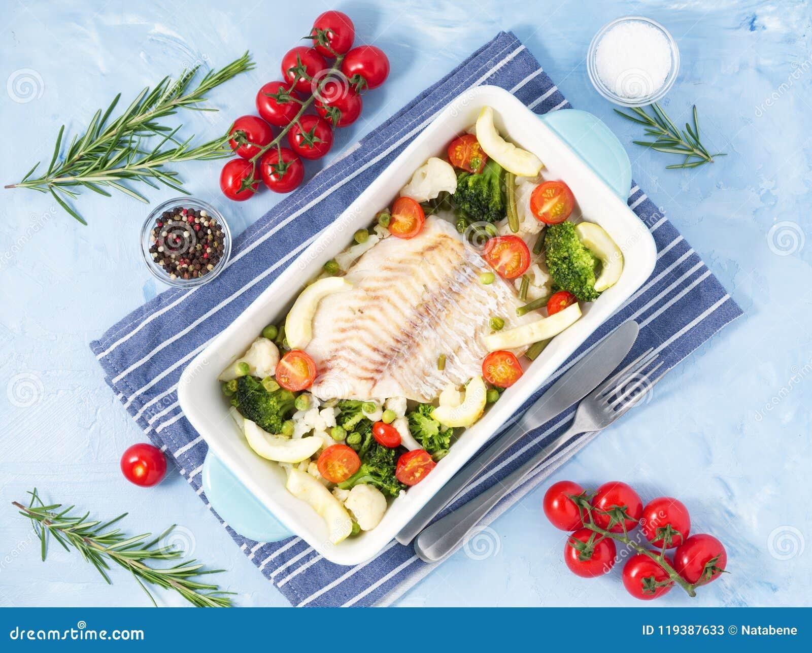 Vissenkabeljauw in blauwe oven met groenten wordt gebakken - broccoli, tomaten die Gezond dieetvoedsel Arduinsteenachtergrond, ho