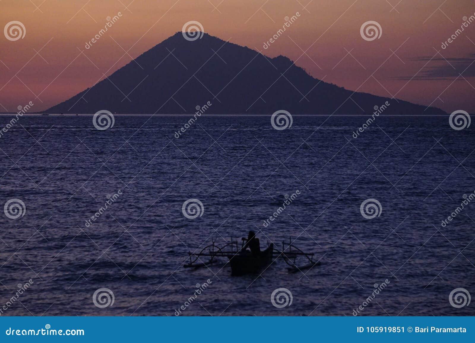 Visser Alone met achtergrond van het Eiland van Manado Tua