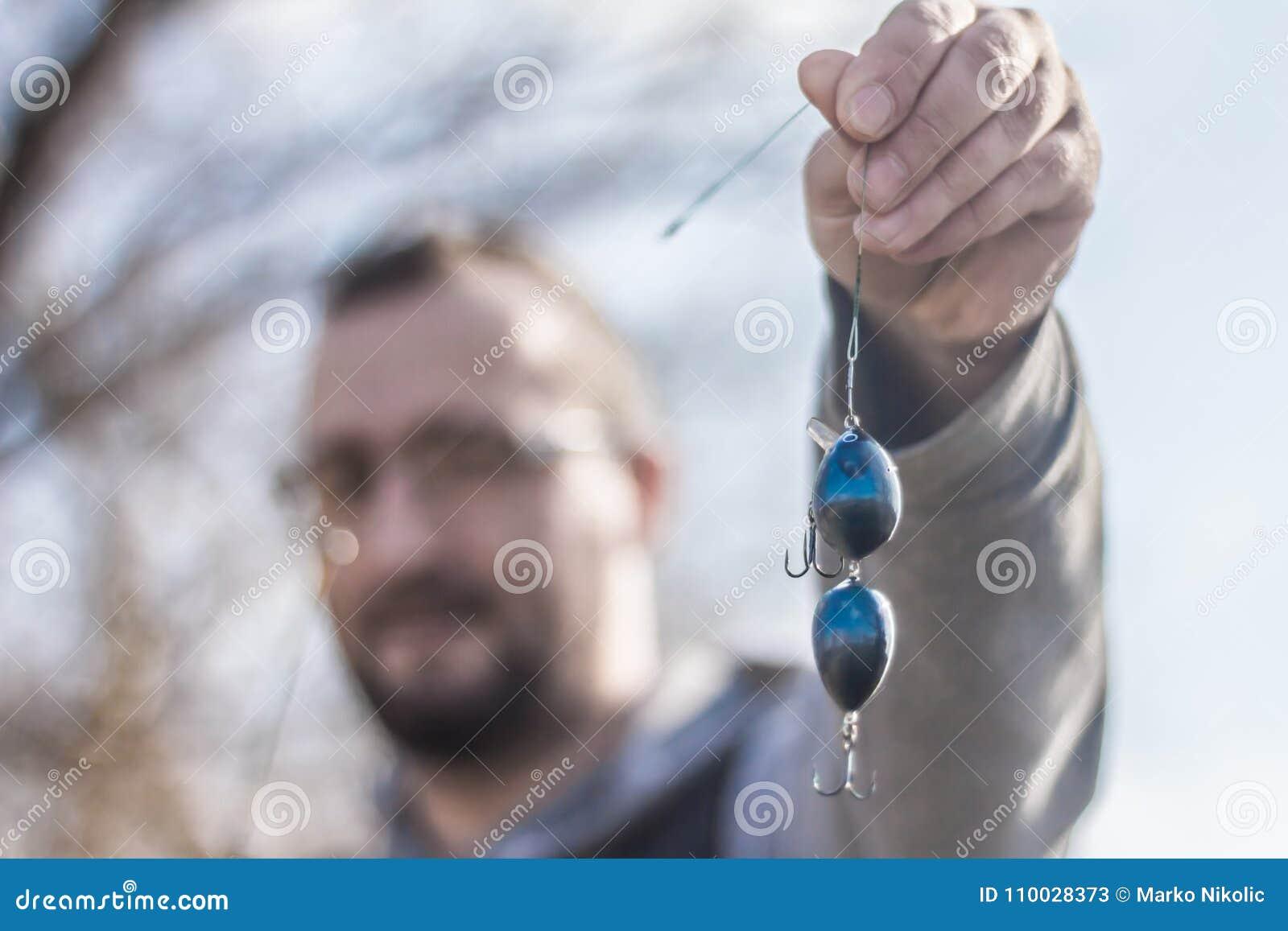 Visser die een naar maat gemaakte haak en aas houden