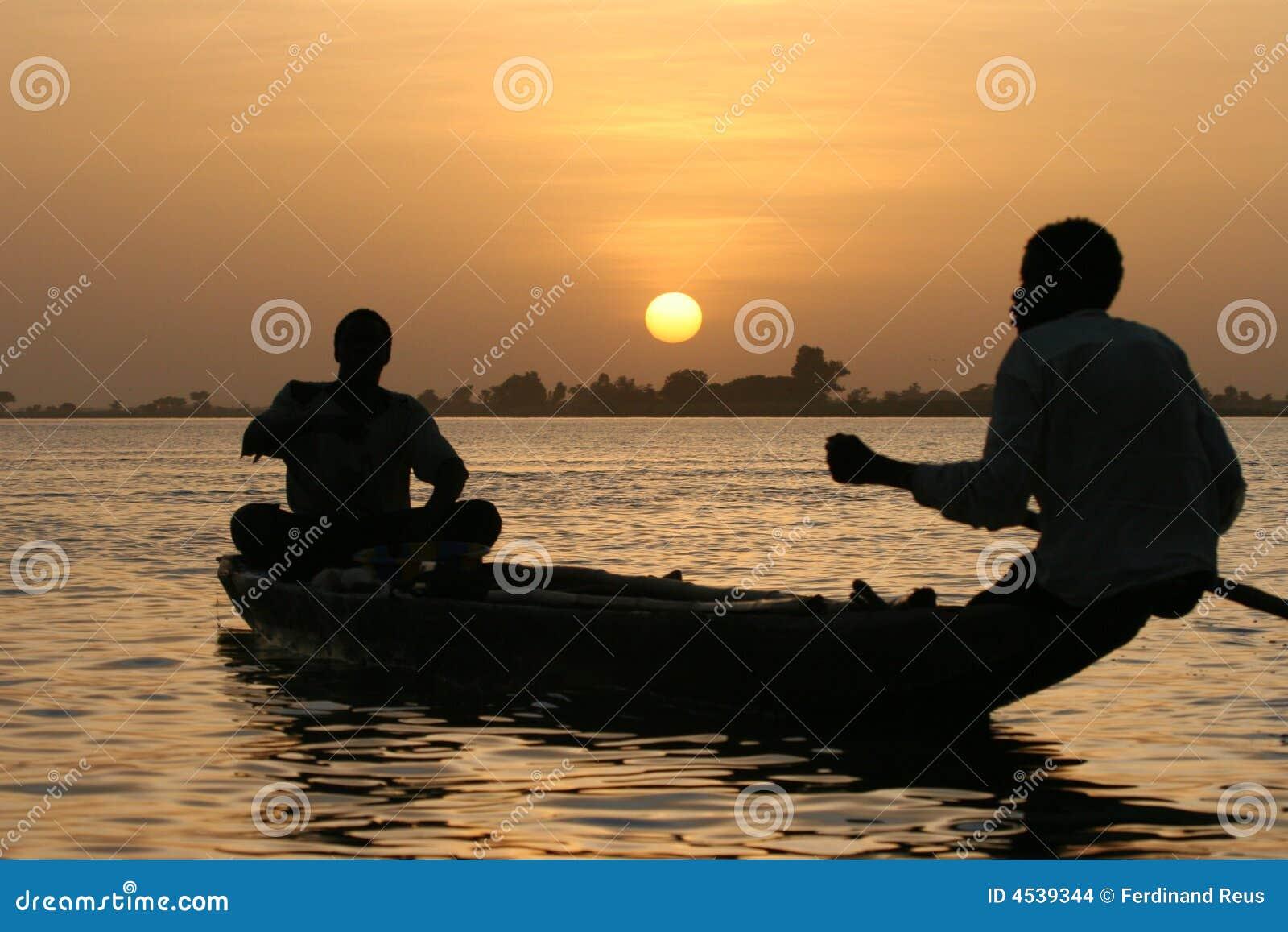 Vissers die een meer kruisen bij zonsondergang