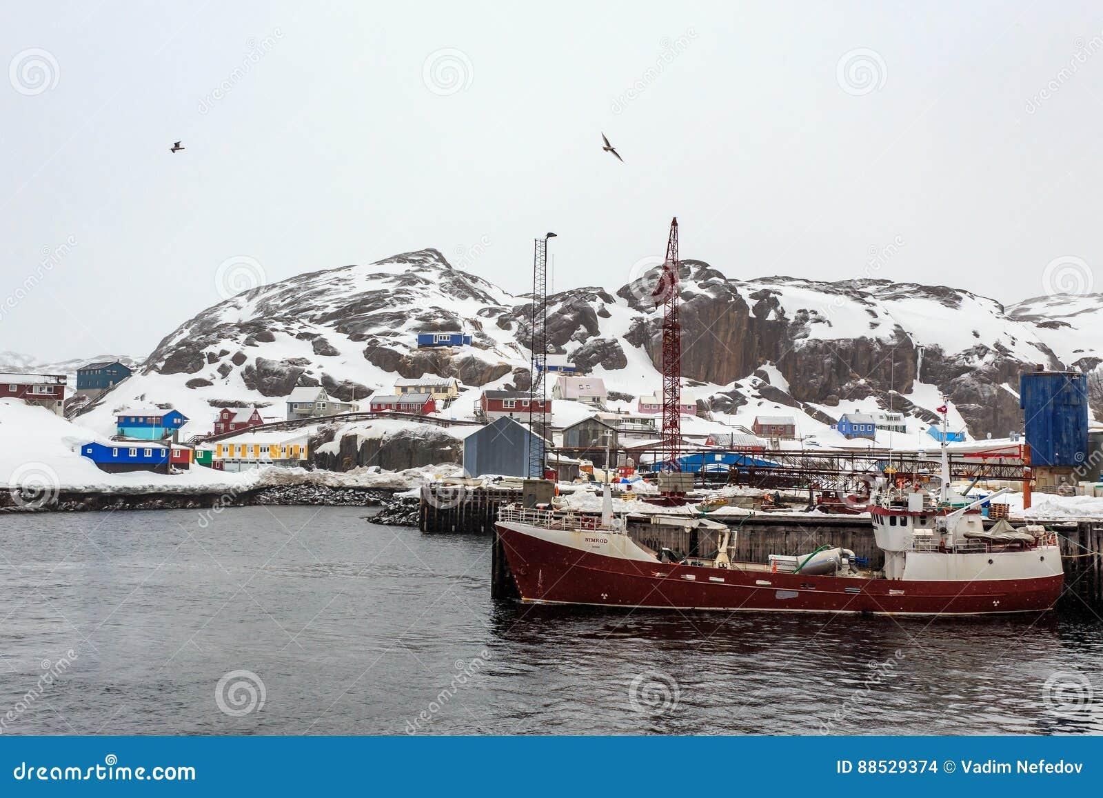 Vissersboot bij de pijler van Maniitsoq-dorp met kleurrijke hous