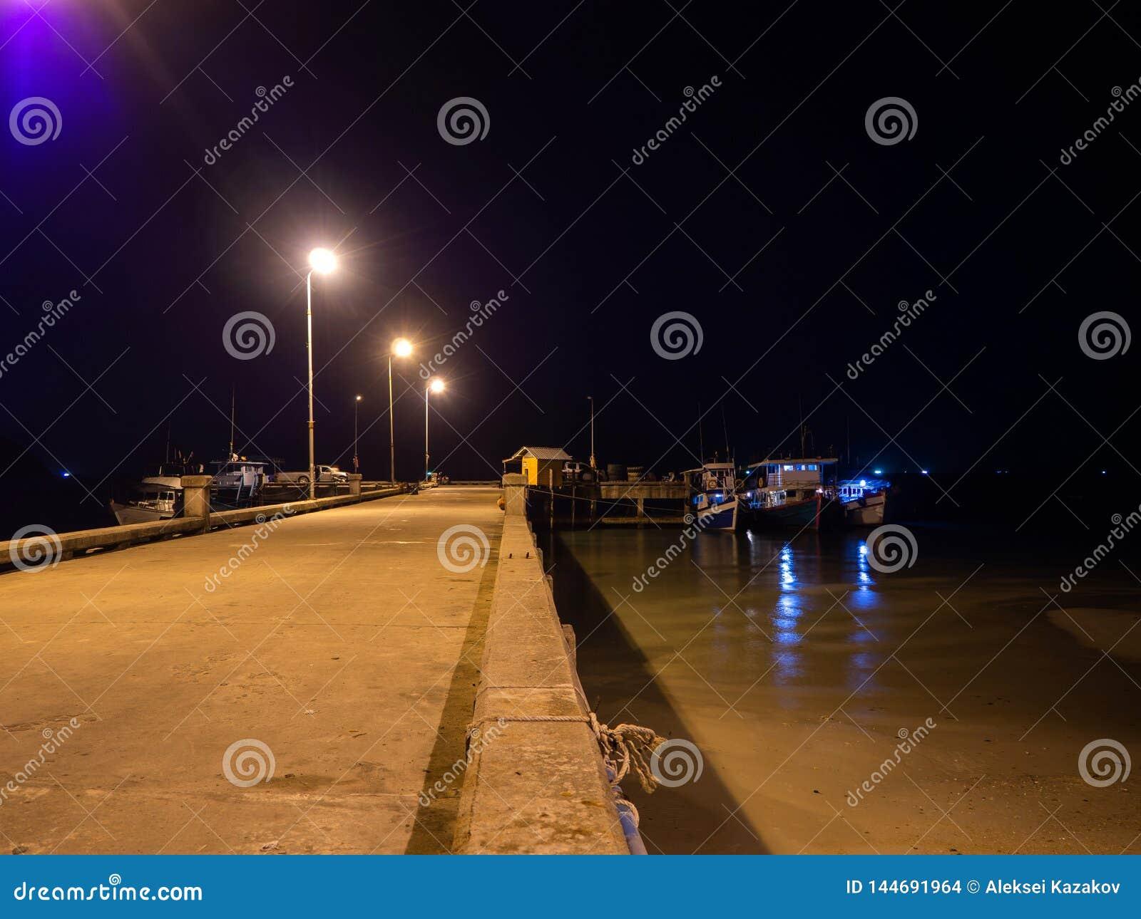 Vissersboten die zich bij nacht bij de pijler bevinden