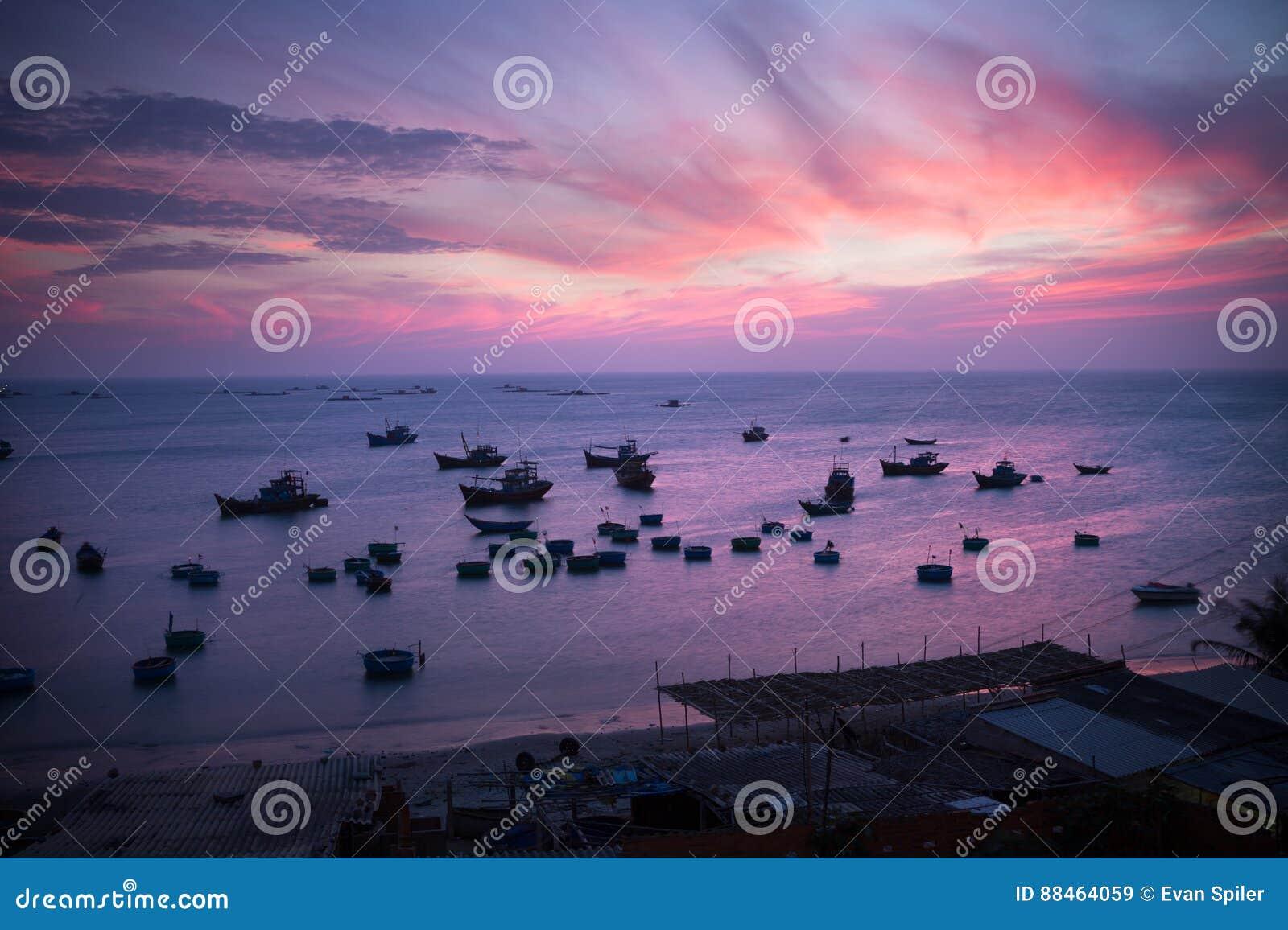 Vissersboten en manden bij zonsondergang