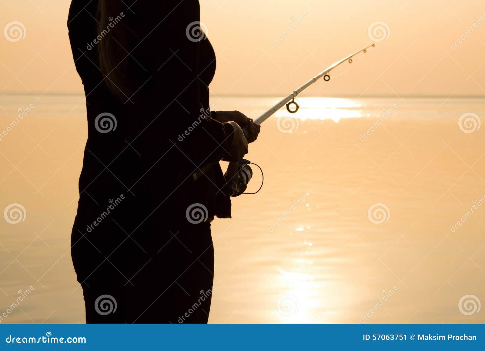 Visserssilhouet bij zonsondergang dichtbij het overzees met een hengel