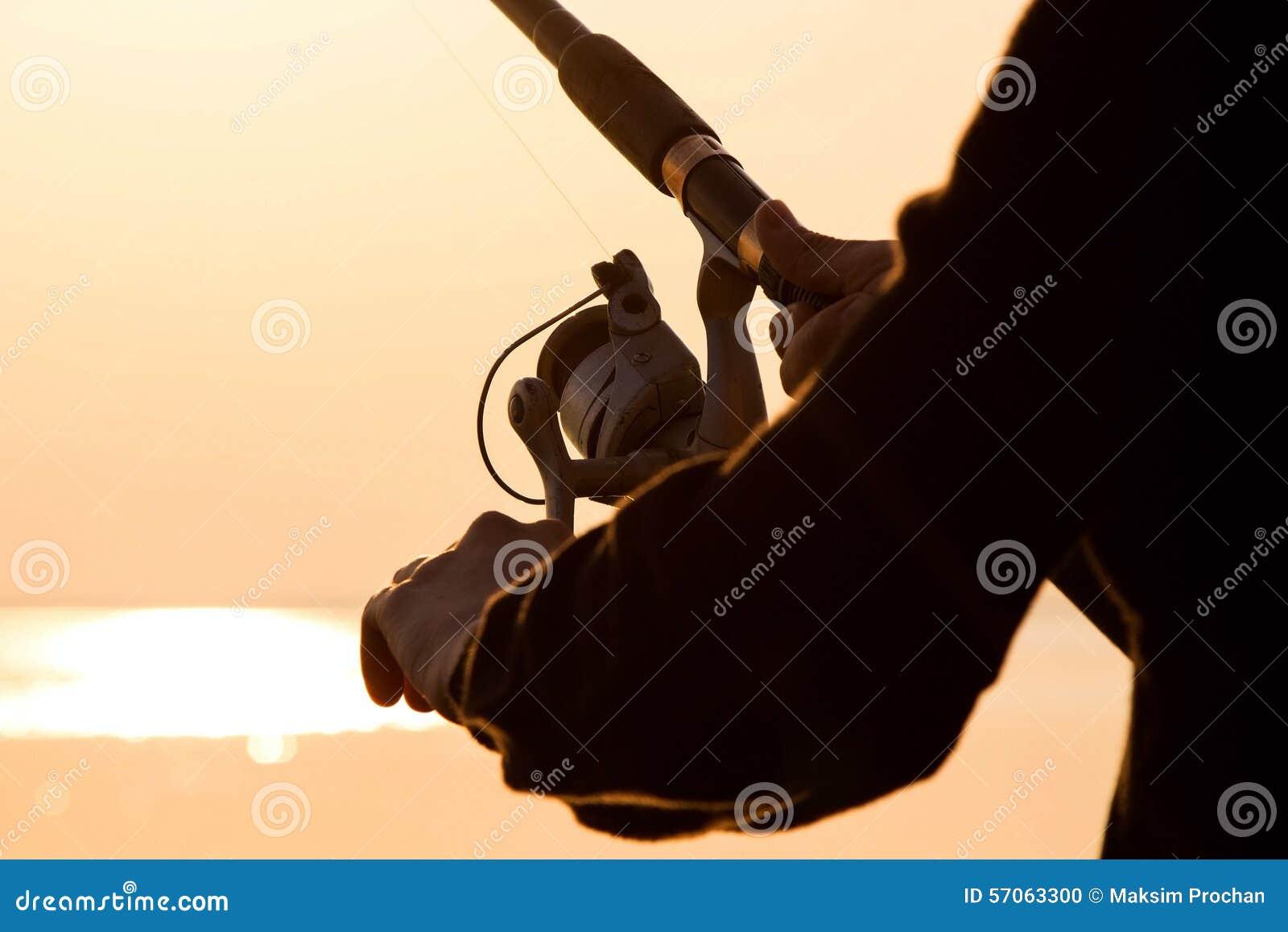 Visserssilhouet bij zonsondergang met een hengel