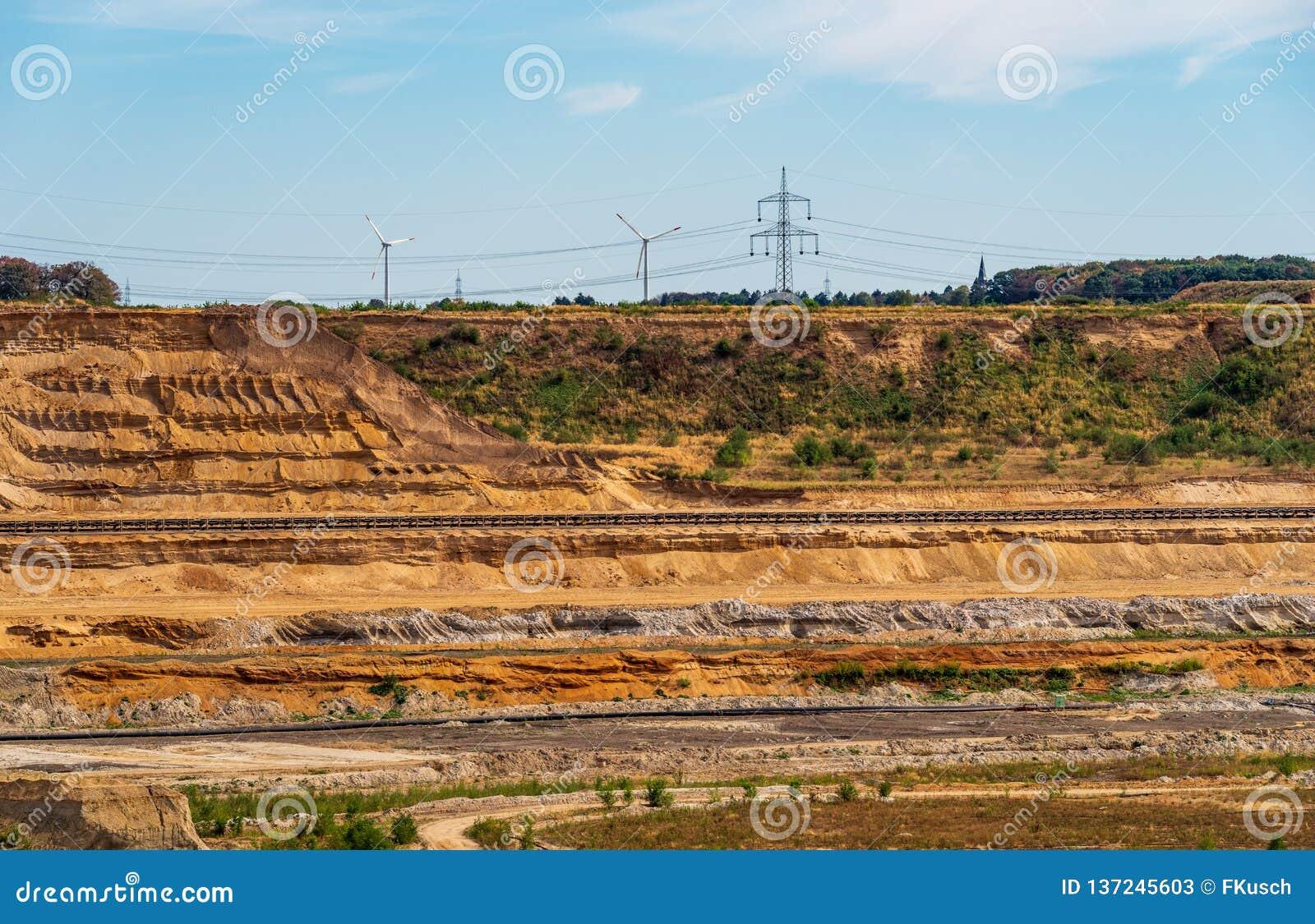A vista à borda de uma área de mineração com correias transportadoras, energias eólicas do lignite roda no fundo