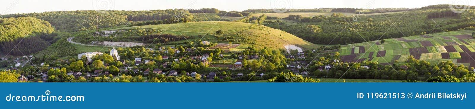 Vista aérea amplia hermosa del pequeño pueblo entre jardines verdes, panorama remendado de los campos de la oscuridad y del bosqu