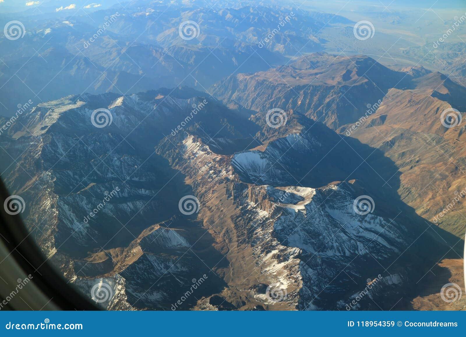 A vista aérea bonita da neve tampou a cordilheira considerada da janela do avião
