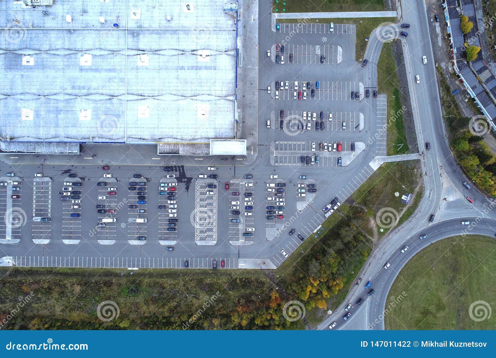 Vista aérea da alameda do supermercado da paisagem da cidade e da construção grande, parque de estacionamento com carros estacion