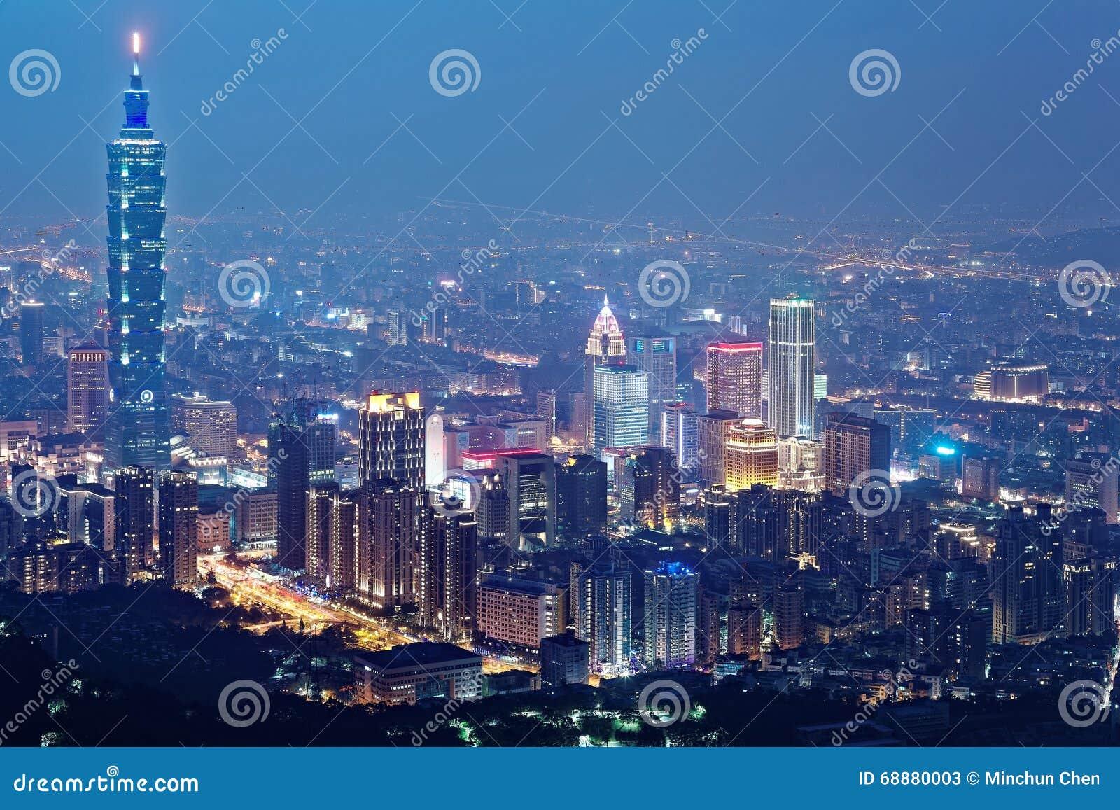 Vista aérea da cidade de Taipei no crepúsculo da noite com o marco de Taipei que está alto entre arranha-céus no distrito do anún
