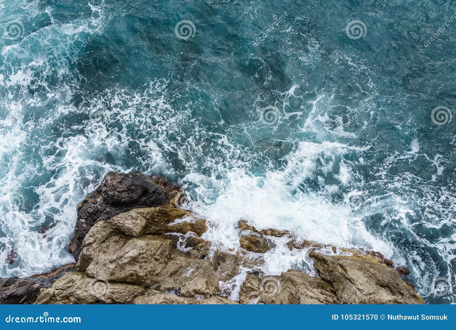 Vista aérea da onda de oceano que deixa de funcionar no penhasco rochoso com spr branco