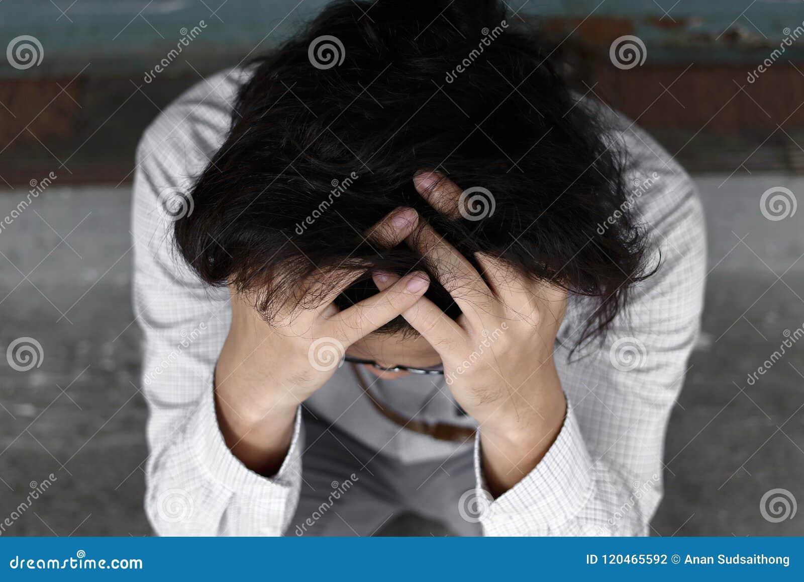 Vista aérea de la cara asiática joven de la cubierta del hombre de negocios de la ansiedad confusa con las manos